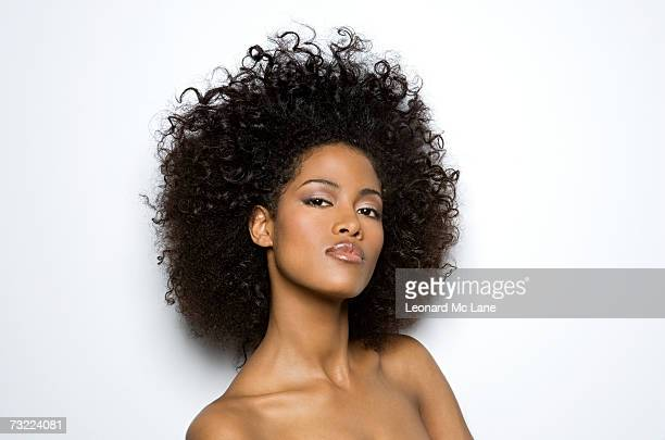 Naked woman standing against white background, portrait, close-up
