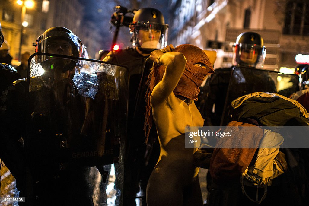 A naked woman stands in front of riot police during a demonstration against the new LGV Lyon-Turin project, on December 3, 2012 in Lyon, on the sideline of the 30th France-Italy annual summit.