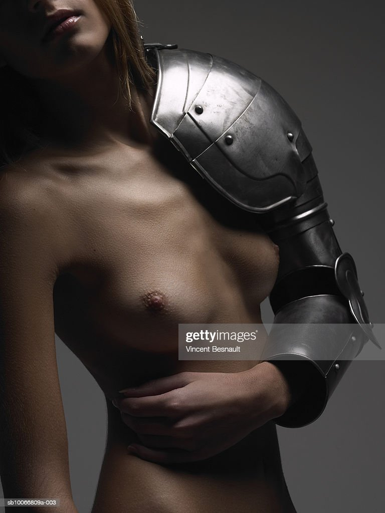 Naked woman wearing body armour on arm, close-up, mid section : Stock Photo