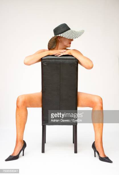 Naked Woman Wearing Hat While Sitting On Chair Against White Background
