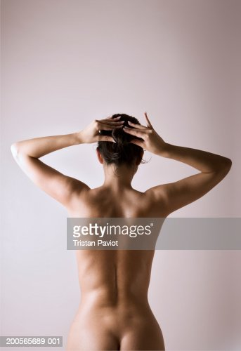 Naked woman with hand in hair, rear view : Stock Photo