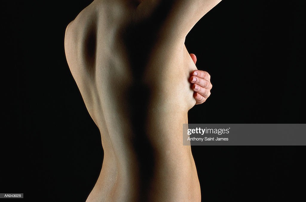 Naked young woman doing breast examination, mid section, rear view : Stock Photo