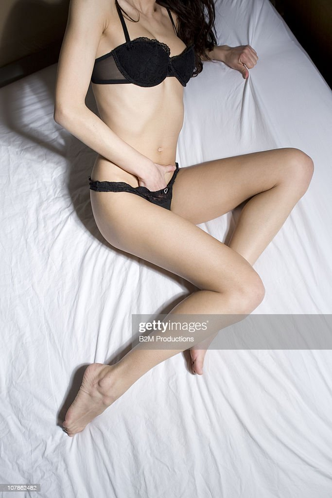 Naked young woman in bed, hand between leg