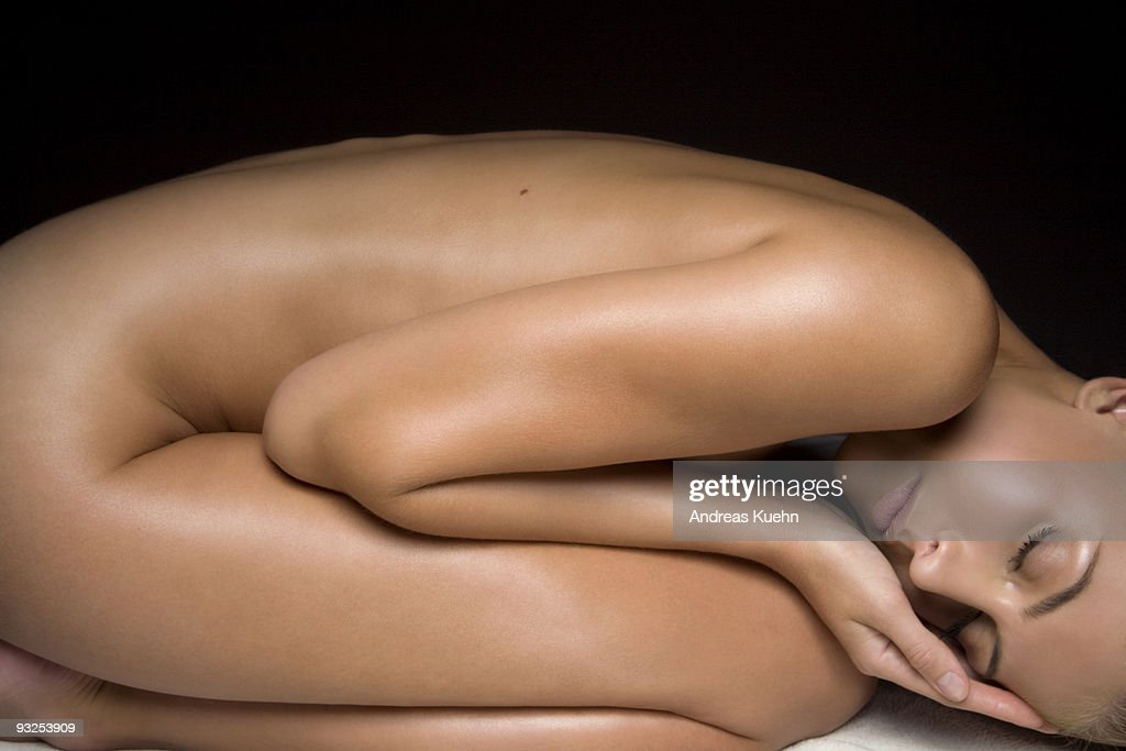 Naked young woman in fetal position, side view. : Stock Photo