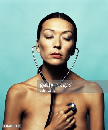 Naked young woman, listening with stethoscope, eyes closed : Stock Photo