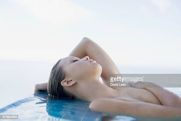 Naked young woman lying in pool with eyes closed