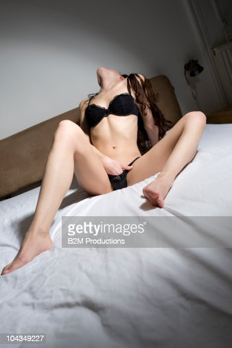 Naked young woman on bed, hand between leg