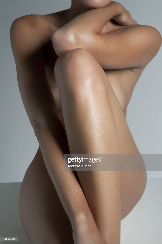 Naked young woman sitting, front view. : Stock Photo