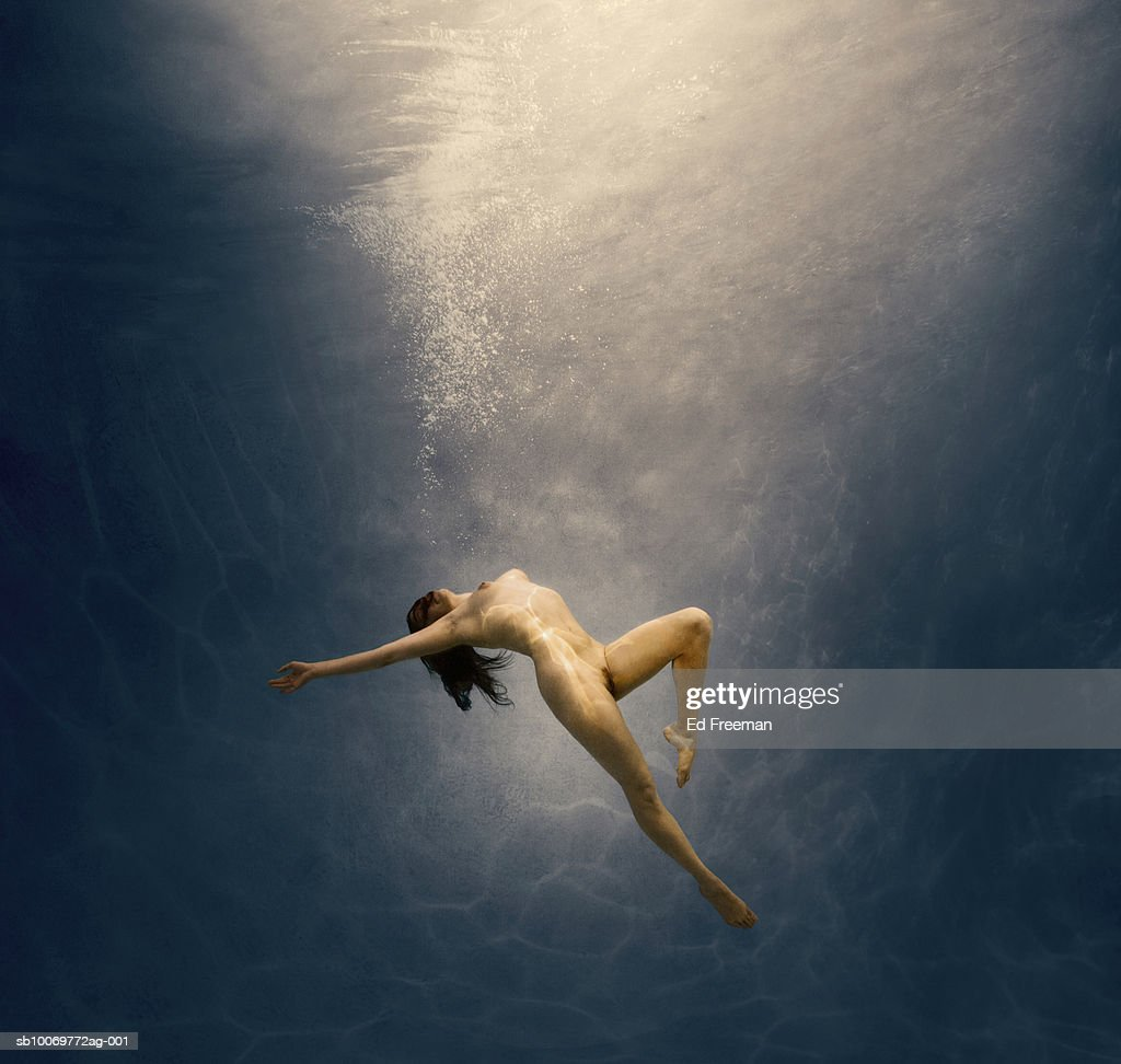 Naked young woman swimming under water : Stock Photo