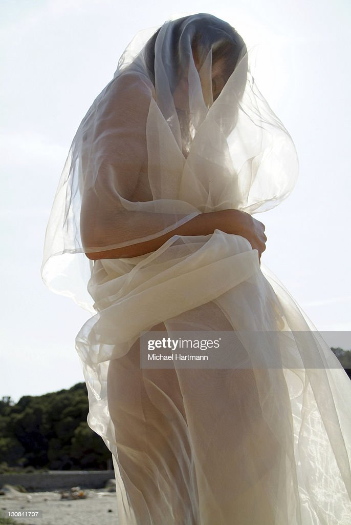 Naked young woman wrapped in transparent cloth on the beach in Mallorca, Spain, Europe : Stock Photo