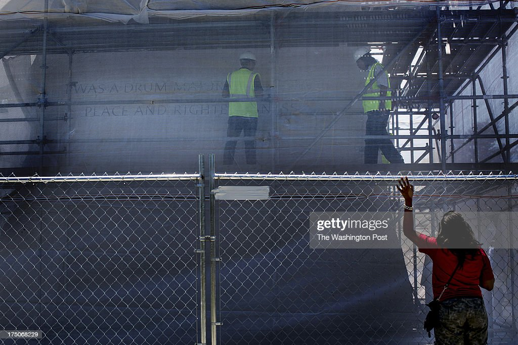 Nakeesha Wilson from Savannah, Georgia, watches stone cutters chip away at the controversial 'drum major' inscription to be removed on the Martin Luther King Memorial in Washington, DC, Monday, July 29, 2013.