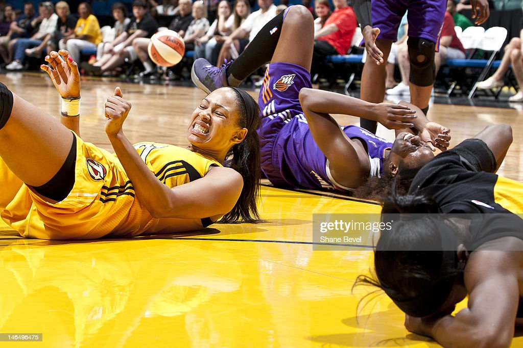 Nakia Sanford of the Phoenix Mercury and Jennifer Lacy and Scholanda Dorrell of the Tulsa Shock wince on the ground after colliding in midair during...