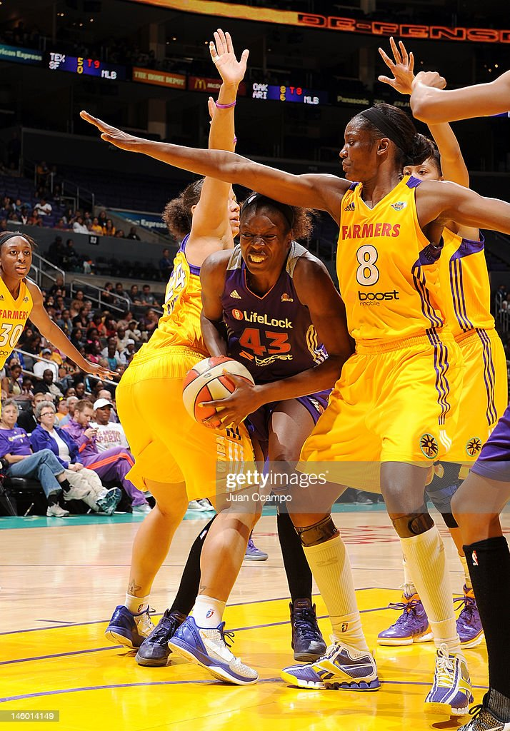 Nakia Sanford of the Phoenix Mercury splits the defense of April Sykes and DeLisha MiltonJones of the Los Angeles Sparks at Staples Center on June 8...