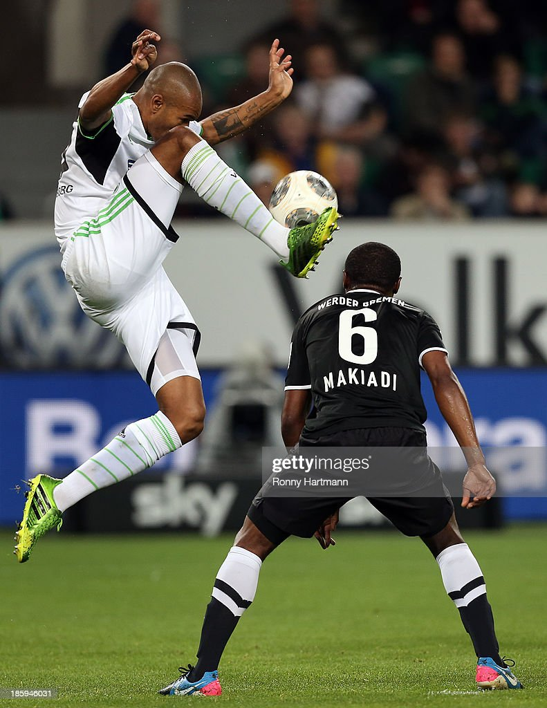 Naldo (L) of Wolfsburg and <a gi-track='captionPersonalityLinkClicked' href=/galleries/search?phrase=Cedrick+Makiadi&family=editorial&specificpeople=635003 ng-click='$event.stopPropagation()'>Cedrick Makiadi</a> of Bremen vie for the ball during the Bundesliga match between VfL Wolfsburg and Werder Bremen at Volkswagen Arena on October 26, 2013 in Wolfsburg, Germany.
