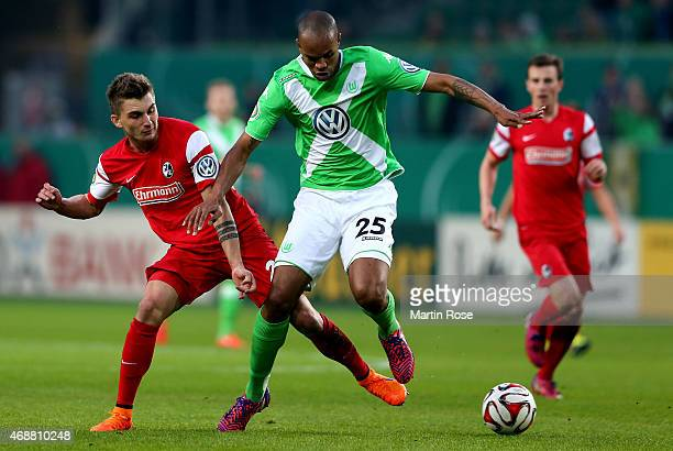 Naldo of Wolfsburg and Maximilian Philipp of Freiburg battle for the ball during DFB Cup Quarter Final match between VfL Wolfsburg and SC Freiburg at...