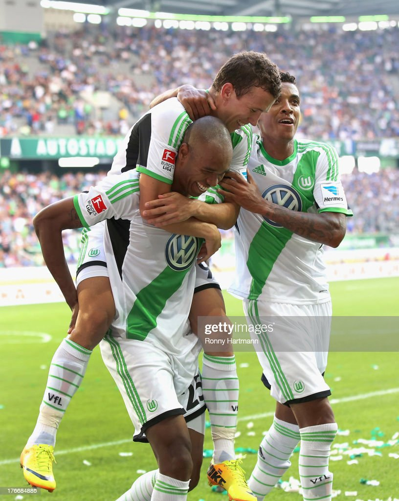 Naldo of Wolfsburg celebrates with teammates Ivan Perisic and Luiz Gustavo after scoring their third goal during the Bundesliga match between VfL...
