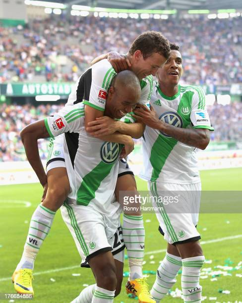 Naldo of Wolfsburg celebrates with teammates Ivan Perisic and Luiz Gustavo after scoring their third goal during the Bundesliga match between VfL...