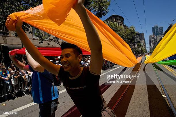 Nam Nguyen carries part of a colored cloth flag as he takes part in the 37th annual LBGT Pride Parade on June 24 2007 in San Francisco California...