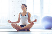 Young beautiful young woman keeping eyes closed while sitting in lotus position in front of window at gym