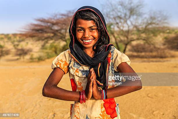 Namaste! Portrait of happy Indian girl in desert village, India