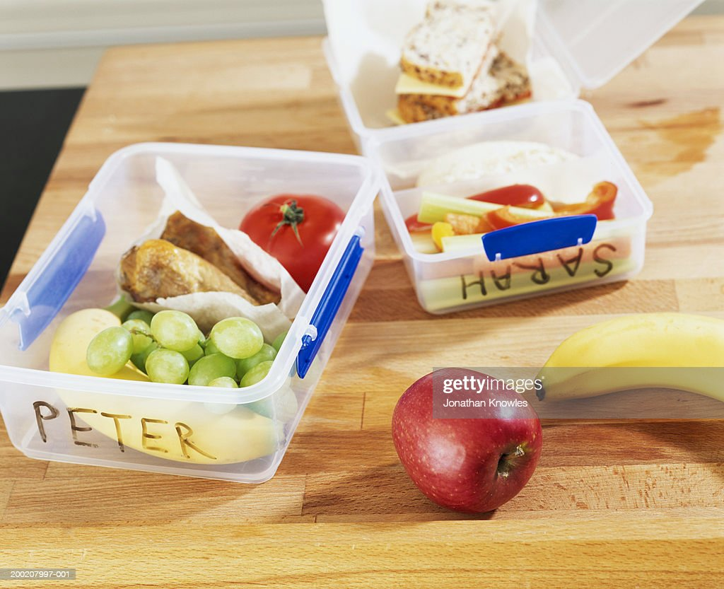 Named packed lunches on table, close-up
