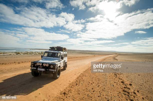 Namibia Africa Land Rover Defender 110 driving on the road