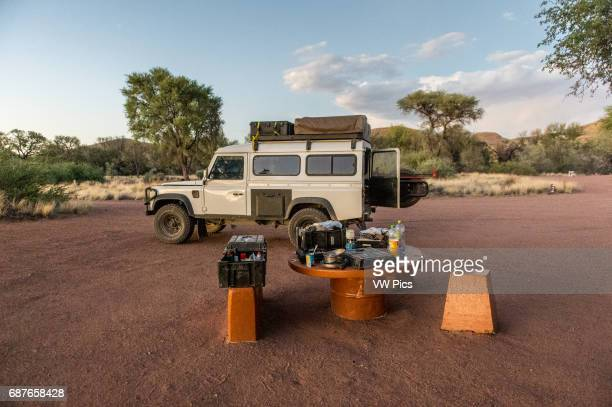Namibia Africa Land Rover Defender 110 parked at a designated campground setting up camp for the night
