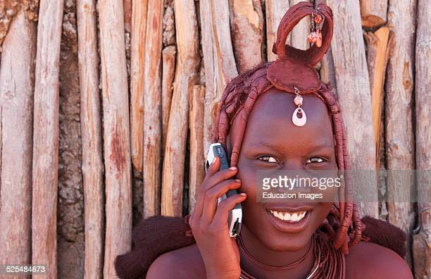 Namibia Africa remote nomadic Himba tribe young women with braids on modern cell phone and traditional dress in desert of Hartmann Berge in Namib...