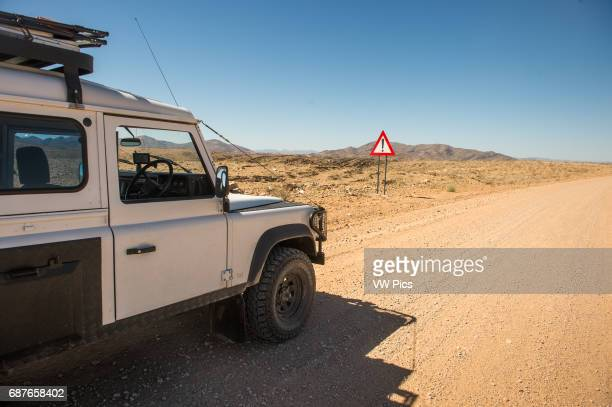 Namibia Africa Warning sign in the desert with a mountain in the distance and a Land Rover Defender 110 parked in front of it