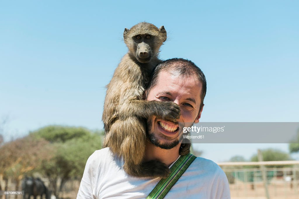 Namibia, man with a baby baboon on his shoulder