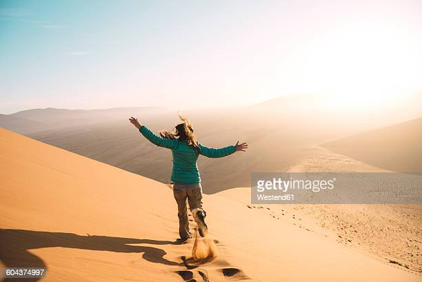 Namibia, Namib Desert, Sossusvlei, Woman running down the Dune 45 at sunrise