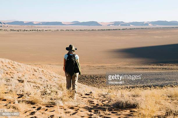 Namibia, Namib Desert, Sossusvlei, Woman with hat and backpack looking at the horizon