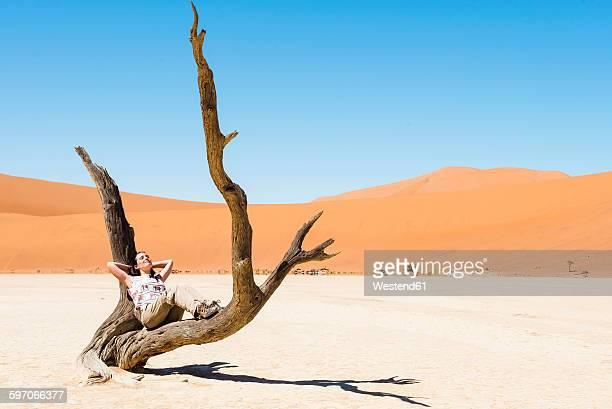 Namibia, Namib Desert, woman resting in dead tree in Deadvlei