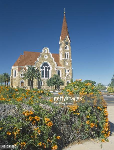 Namibia Windhoek Christuskirche church exterior viewed from Parliament Gardens with a flowering bush in the foreground