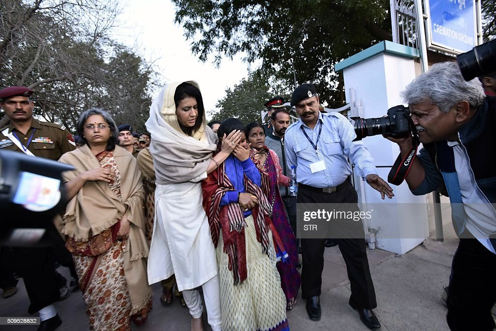 Namita Suhag (centre L), the wife of Indian army chief Dalbir Singh, consoles the wife (C) of avalanche survivor Hanumanthappa Koppad in New Delhi on February 11, 2016. Indian army soldier Koppad, who was rescued nearly a week after being buried in eight metres (25 feet) of snow by a deadly Himalayan avalanche, died in hospital on February 11 of his injuries, the army said. AFP PHOTO / AFP / STR