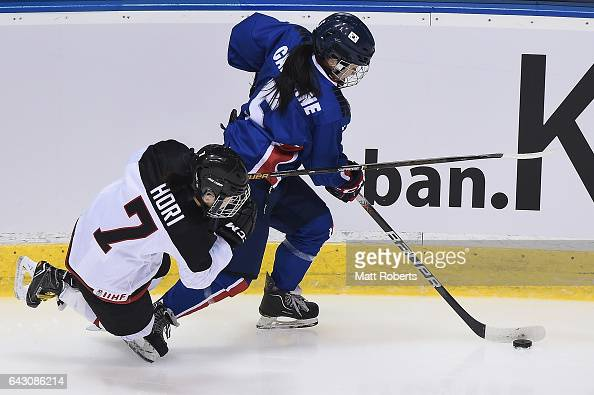 Nancy Caroline Park of Korea and Mika Hori of Japan battle for the puck during the Women's Ice Hockey match between Japan and South Korea on day...