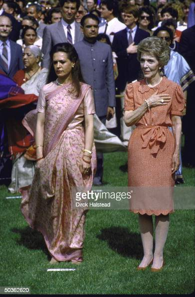 Nancy Reagan holds hand over heart during playing of national anthem while standing with Sonia Gandhi at White House ceremony