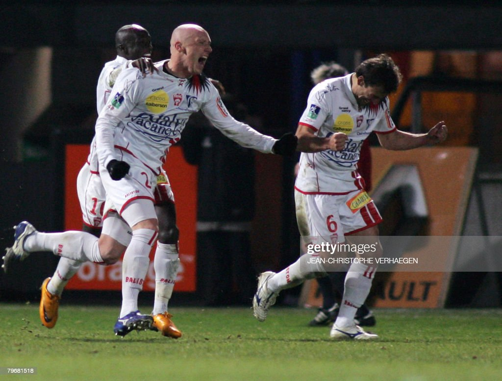 Nancy's defender Sebastien Puygrenier celebrates next to his teammates Issiar Dia and Pascal Berenguer after scoring a penalty kick in front of...