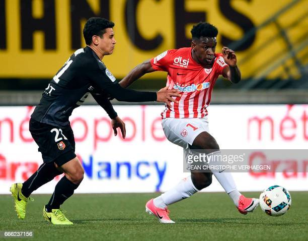 Nancy's French defender Faitout Maouassa vies for the ball with Rennes' French midfielder Benjamin Andre during the French L1 football match between...