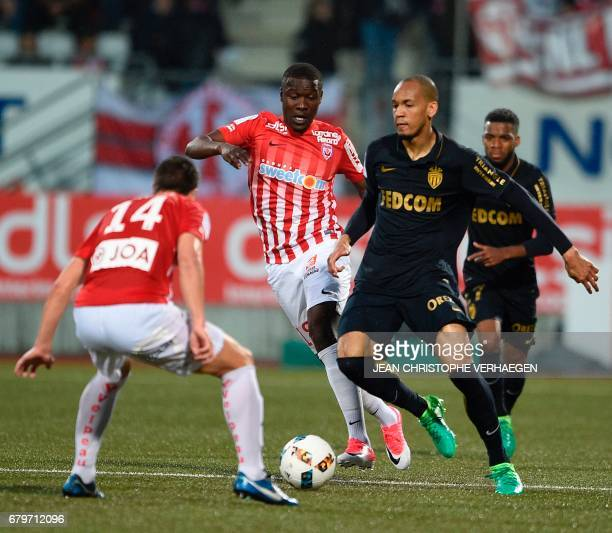 Nancy's French defender Joffrey Cuffaut and Nancy's French defender Julien Cétout vie for the ball with Monaco's French midfielder Fabinho during the...