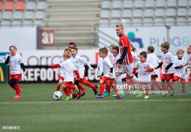Nancy's French forward Alexis Buzin plays with children at the start of the 50 hours football match on March 24 2017 at Marcel Picot stadium in...