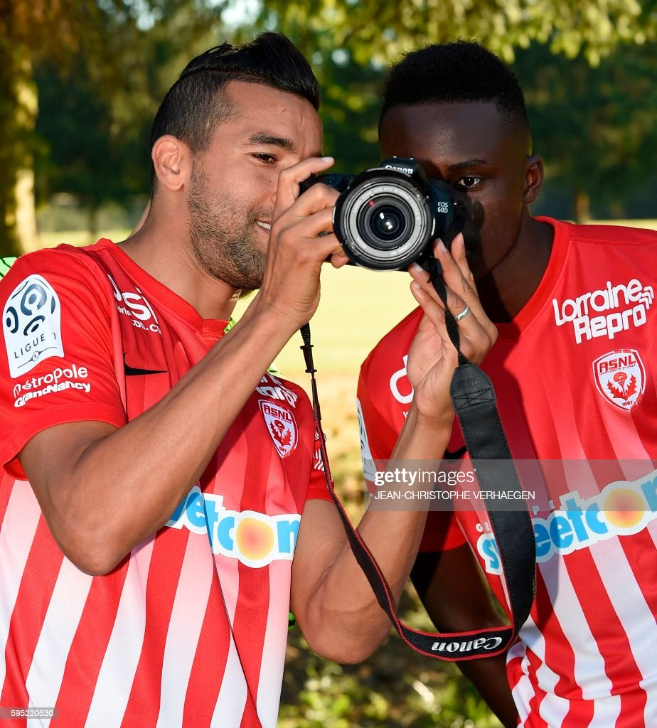 Nancy's Moroccan forward Youssouf Hadji looks at pictures on a camera beside Nancy's French defender Modou Diagne during the presentation of the...