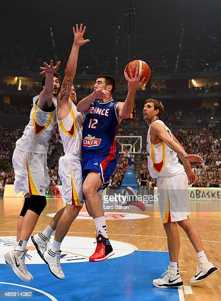 Nando de Colo of France is challenged by Tibor Pleiss Anton Gavel and Dirk Nowitzki of Germany during the Men's Basketball friendly match between...