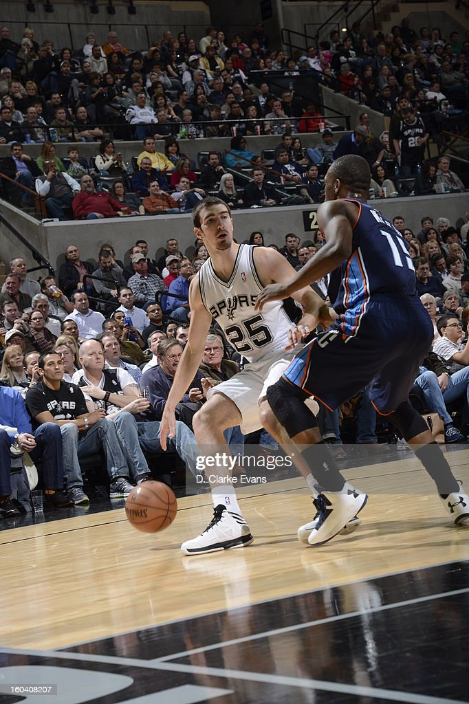 Nando de Colo #25 of the San Antonio Spurs dribbles past <a gi-track='captionPersonalityLinkClicked' href=/galleries/search?phrase=Kemba+Walker&family=editorial&specificpeople=5042442 ng-click='$event.stopPropagation()'>Kemba Walker</a> #15 of the Charlotte Bobcats on January 30, 2013 at the AT&T Center in San Antonio, Texas.