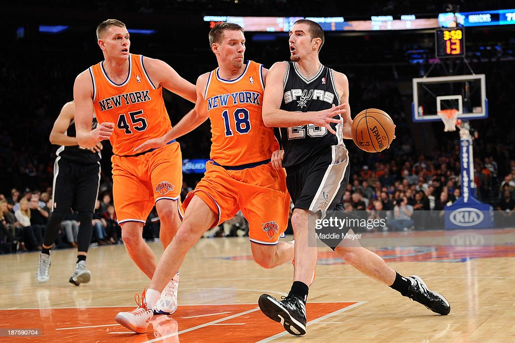 Nando de Colo #25 of the San Antonio Spurs drives past <a gi-track='captionPersonalityLinkClicked' href=/galleries/search?phrase=Beno+Udrih&family=editorial&specificpeople=202616 ng-click='$event.stopPropagation()'>Beno Udrih</a> #18 of the New York Knicks and <a gi-track='captionPersonalityLinkClicked' href=/galleries/search?phrase=Cole+Aldrich&family=editorial&specificpeople=4226189 ng-click='$event.stopPropagation()'>Cole Aldrich</a> #45 of the New York Knicks during the second half at Madison Square Garden on November 10, 2013 in New York City. The Spurs defeat the Knicks 120-89.