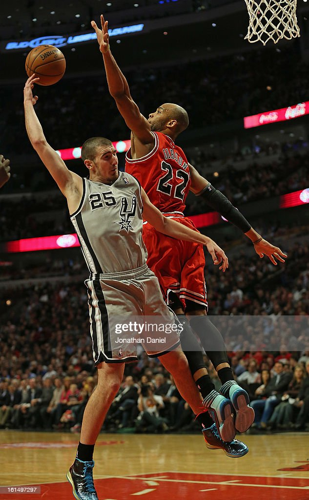 Nando De Colo of the San Antonio Spurs passes the ball around Taj Gibson of the Chicago Bulls at the United Center on February 11 2013 in Chicago...