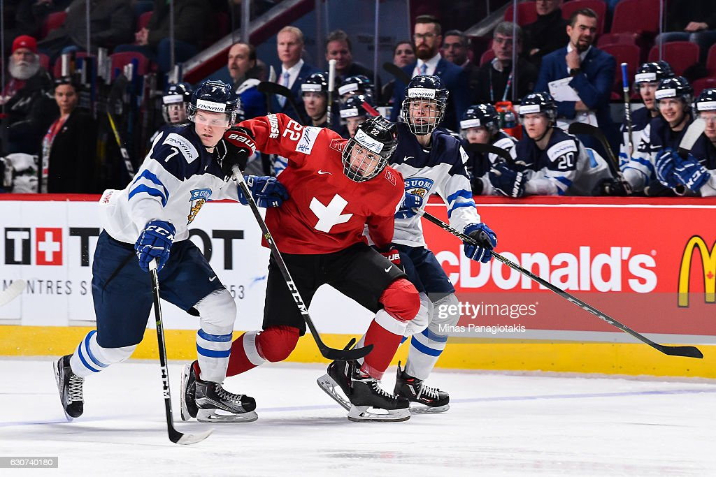 Nando Eggenberger #22 of Team Switzerland squeezes past Olli Juolevi #7 and Miro Heiskanen #2 of Team Finland during the 2017 IIHF World Junior Championship preliminary round game at the Bell Centre on December 31, 2016 in Montreal, Quebec, Canada. Team Finland defeated Team Switzerland 2-0.