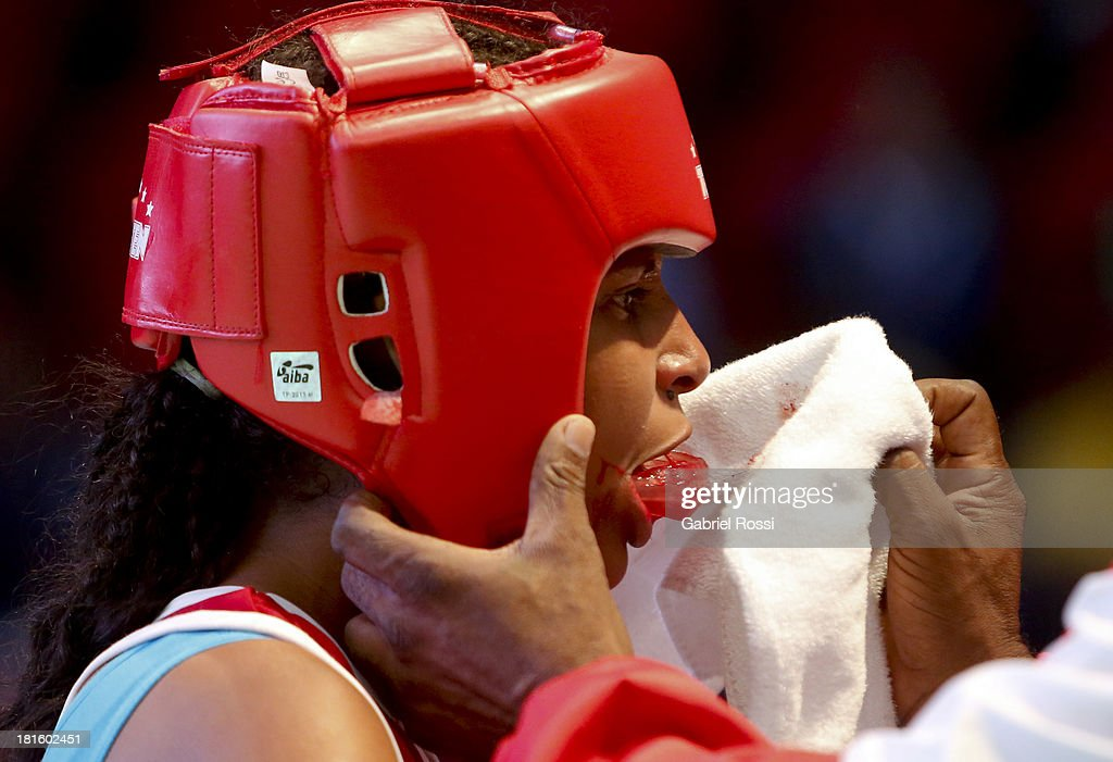 Naneth Carrion (red) of Panama takes off her boxing mouthguard during the Women's 48kg Boxing Qualifications as part of the I ODESUR South American Youth Games at Coliseo Miguel Grau on September 22, 2013 in Lima, Peru.