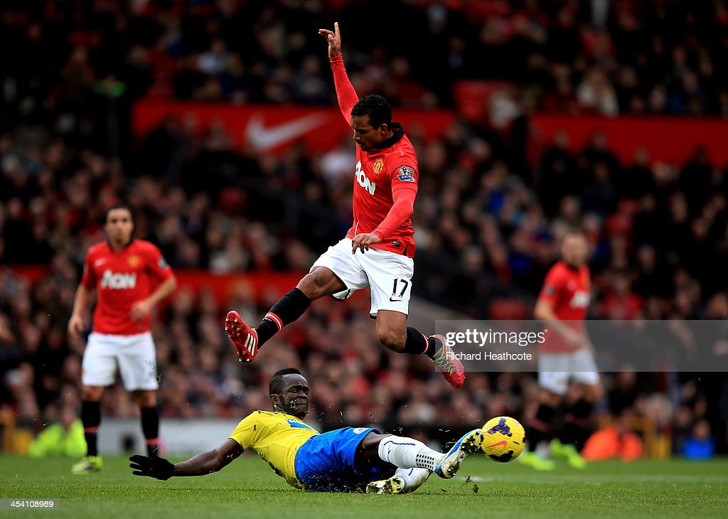 Nani of Manchester United hurrdles the tackle from Cheik Ismael Tiote of Newcastle during the Barclays Premier League match between Manchester United and Newcastle United at Old Trafford on December 7, 2013 in Manchester, England.