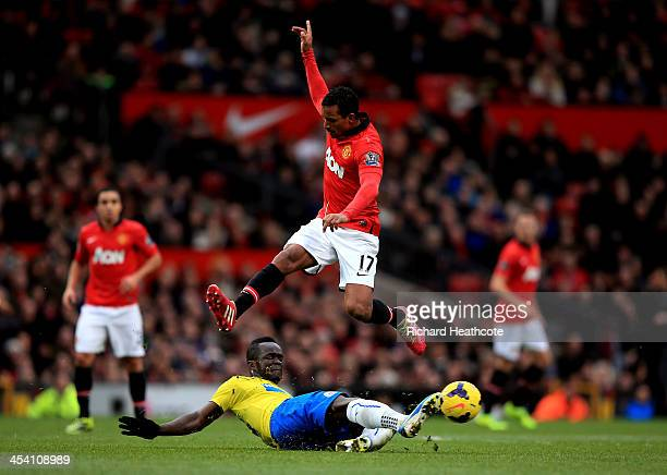 Nani of Manchester United hurrdles the tackle from Cheik Ismael Tiote of Newcastle during the Barclays Premier League match between Manchester United...